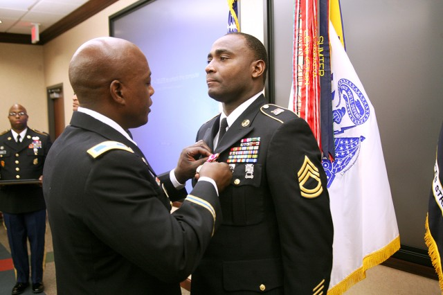 """Col. Lester """"JC"""" Campbell, deputy chief of staff, G-8, U.S. Army Space and Missile Defense Command/Army Forces Strategic Command, pins the Meritorious Service Medal onto Sgt. 1st Class James F. Epps, Sexual Harassment/Assault Response Prevention program manager, SMDC, during Epps' retirement from active duty Aug. 9 at the command's Redstone Arsenal, Ala., headquarters. Epps retires with 20 years of service."""