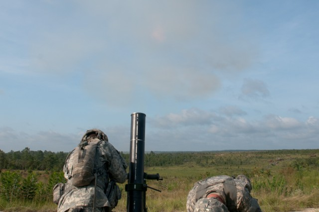 Spc. Delorean L. Graham of Brown Deer, Wis., and Pfc. Joshua J. Wertz, of Dover, Pa., mortarmen with the 82nd Airborne Division's 1st Brigade Combat Team, brace themselves as a round leaves their mortar tube, Aug. 9, on Fort Bragg, N.C. The mortarmen fired more than 30 rounds as part of a professional development training session for leaders in Headquarters and Headquarters Company, 1st Battalion, 504th Parachute Infantry Regiment. (U.S. Army photo by Staff Sgt. Mary S. Katzenberger)