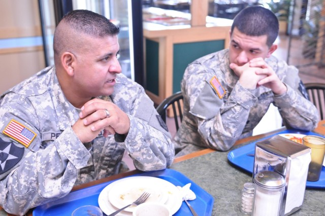 Spc. Jerae Perez, intelligence analyst, 2nd Squadron, 1st Cavalry Regiment, 4th Brigade, 2nd Infantry Division, eats breakfast with his father, Sgt. 1st Class Fernando Perez, platoon sergeant, 14th Engineer Battalion, 555th Engineer Brigade, after a three-mile road march around North Fort, July 7. Jerae was born on JBLM while his father was stationed here 1992-1995. Now at age 20, he's also on active duty and stationed here with his father.