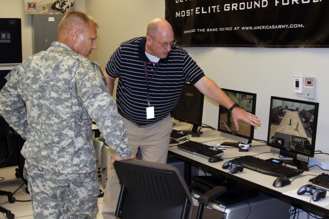 Software engineer Jeff Sallas leads Maj. Gen. Allen Batschelet, commanding general, U.S. Army Recruiting Command, on a tour of the Army Game Studio at Aviation and Missile Research Development and Engineering Center at Redstone Arsenal, Ala.  Here he describes the Virtual Recruiting World, a trainer designed for Army recruiters that replicates career fairs and other engagement opportunities