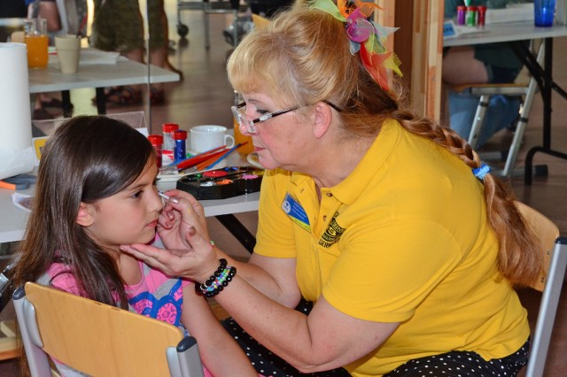 Karen Schaeffer, Wiesbaden Army Community Service relocation readiness assistant, paints Zariah Colon-Pagan's face during the ACS birthday celebration.
