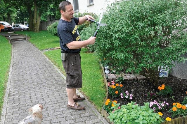 Joe Bednash tends to the flowers and plants in front of his building in Hainerberg Housing.