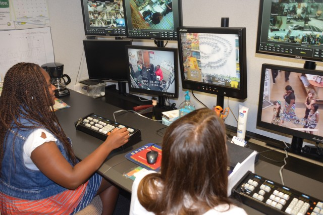 Savanna Ellis and Lauren Din operate security cameras and observe shoppers on a series of video screens at the Fort Lee Exchange Loss Prevention Office during a Teen Camp workshop here Aug. 7. They were part of a group of nine teens attending the American Red Cross and Army Community Service Youth Program, and experienced a behind-the-scenes look at Exchange security in a theft awareness role-playing exercise