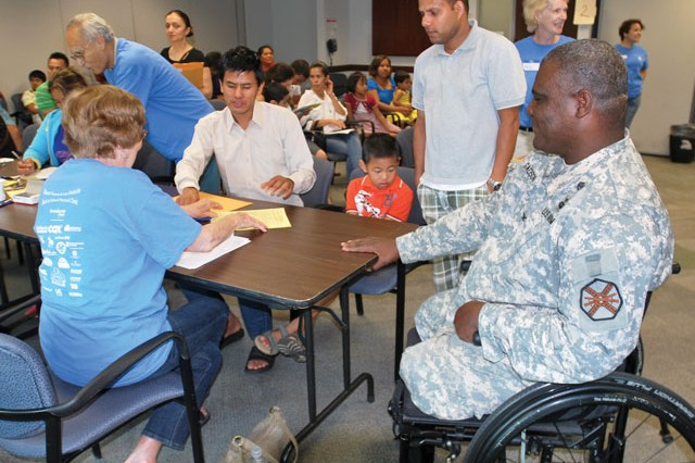 Garrison Commander Col. Gregory D. Gadson helps local Families as they check in their children for Fairfax County's annual back-to-school physicals at South County Health Center in Alexandria, Va., Aug. 10.