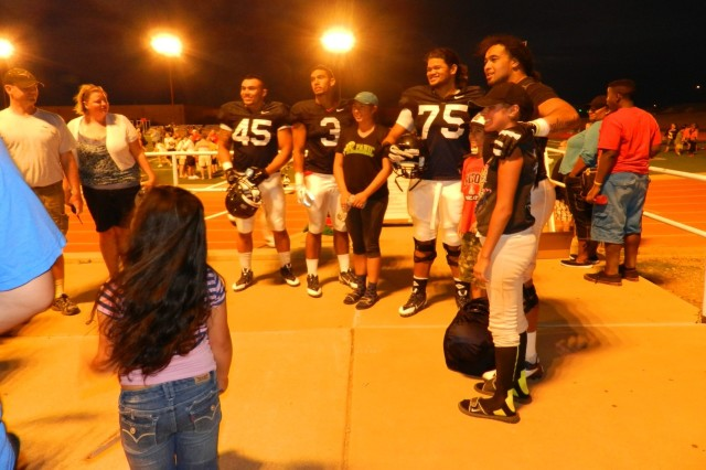 After the sun sets and the bright lights shine upon Bujalski Field, Derrick Turituri, feshman line backer, Daniel Jenkins, senior running back, Kirifi Taula, junior defensive lineman, and Sione Tuihalamaka, senior defensive lineman, take the time after practice to meet some of their fans and even pose with them in some pictures.