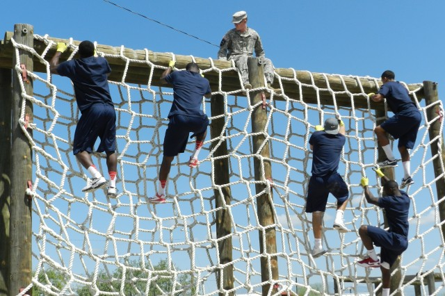 University of Arizona football players climb the cargo net during their obstacle course challenge on Sunday.  Sgt. William Everett, 18th Military Police Detachment, sat atop the netted structure to provide safety for all participants and to boost morale.