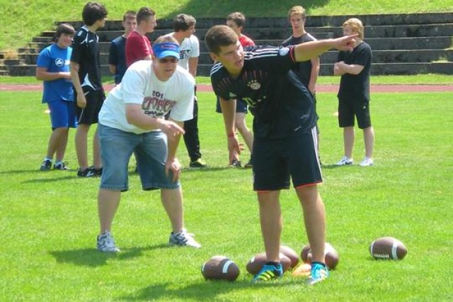 Chris Cornelison, Family and Morale, Welfare and Recreation sports and fitness chief (left), shares strategies on flag football with students of Neumarkt in der Oberpfalz Knabenrealschule, recently.