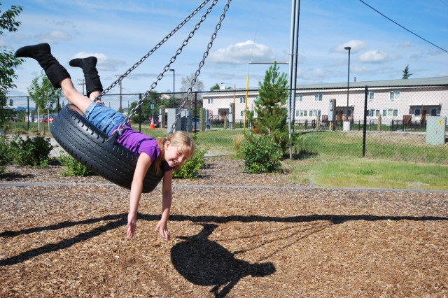 Alexis, daughter of Spc. Jason Krause, 25th Brigade Support Battalion, 1st Stryker Brigade Combat Team, 25th Infantry Division, swings on a tire at the School Age Center July 22.