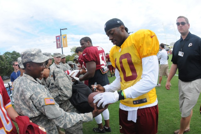 Washington Redskins quarterback Robert Griffin III signs a football for Pvt. J'nai Foreman, 111th Quartermaster Company, Fort Lee, Va., during an Aug. 14 military appreciation event at the Redskins new training camp in Richmond.