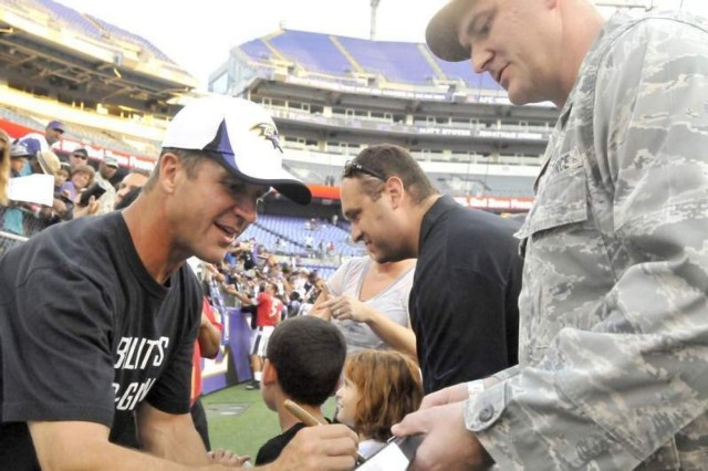 Baltimore Ravens head coach John Harbaugh (left) autographs a team lithograph for Air Force Capt. Andrew Hott following the NFL franchise's military appreciation day held in Baltimore Aug. 11.