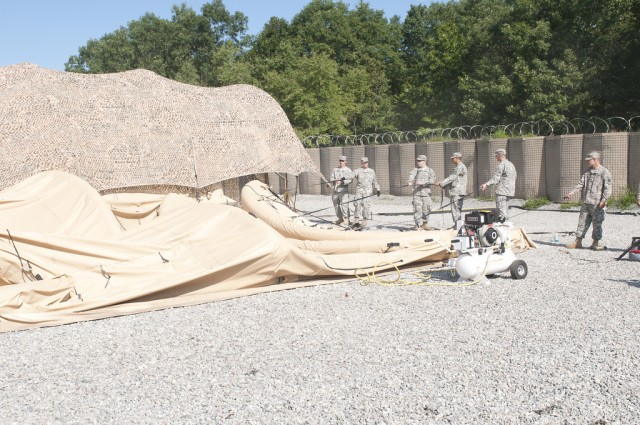 Soldiers set up an air-supported tent