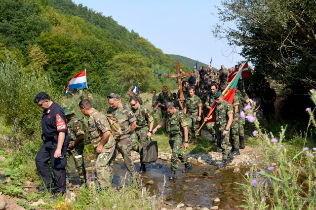 LETNICA, Kosovo - Multinational soldiers from Kosovo Forces cross a creek on their pilgrimage to the Church of the Black Madonna Aug. 15. For the last 400 years people throughout the Balkans have been making the pilgrimage to the church to celebrate the Feast of the Assumption of the Blessed Virgin Mary. (U.S. Army photo by Capt. Randy Ready, 4th Public Affairs Detachment)