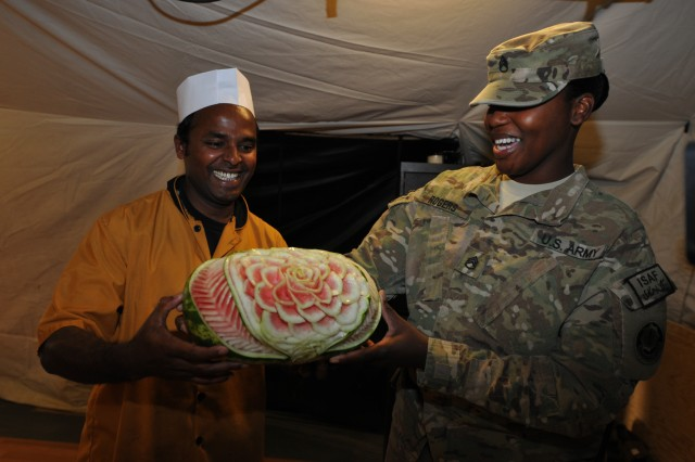 Staff Sgt. Deandria Rogers, senior food operations noncommissioned officer for 1st Squadron, Combined Task Force Dragoon, holds a watermelon prepared by a civilian food specialist Aug. 13, 2013 at Forward Operating Base Zangabad, Afghanistan. Rogers works daily with civilian food service employees to ensure the troops at the base receive three properly prepared meals a day. (U.S. Army Photo by Spc. Joshua Edwards)