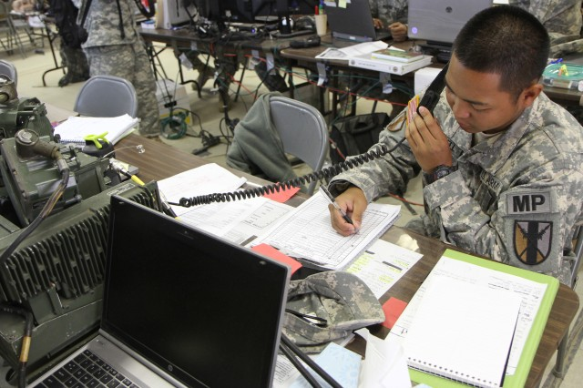 Fort McCoy, Wis. - Spc. Greg Campbell, a military police officer with Headquarters and Headquarters Company, 303rd Maneuver Enhancement Brigade, 9th Mission Support Command, receives a transmission from 467th Engineer Battalion July 23 at Ft McCoy, Wis. The 303rd MEB conducted the warrior exercise, Operation Compass Shield.