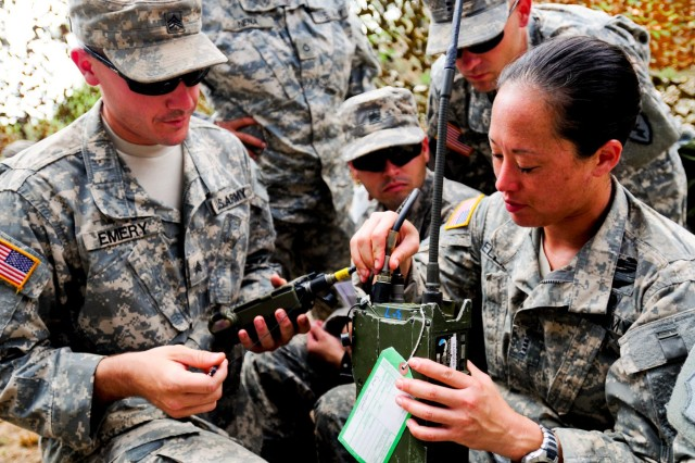 Chief Warrant Officer 2 Christina Hellman, a UH-60 pilot assigned to Company A, 3rd General Support Aviation Battalion, 25th Aviation Regiment, 25th Combat Aviation Brigade, 25th Infantry Division, receives instruction on how to load and operate a radio at the communication and UXO training lane during the 3-25 AVN field training exercise near Dillingham Airfield, Hawaii, Aug. 6.