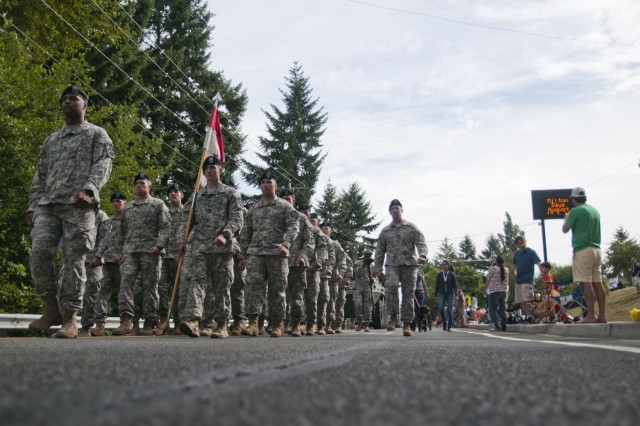 Soldiers with Troop B, 8th Squadron, 1st Cavalry Regiment, 2nd Stryker Brigade Combat Team, 2nd Infantry Division, march through Downtown Milton, Wash., followed closely by their Stryker during the Milton Days Parade, Aug. 17. (Photo by Sgt. Ryan Hohman, 2nd Bde., 2nd Inf. Div.)