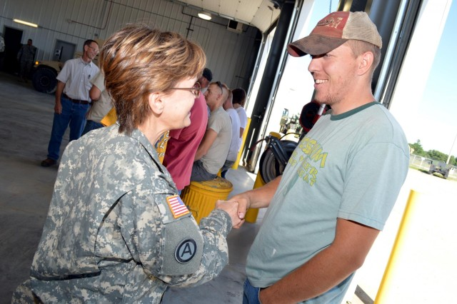 Maj. Gen. Karen E. LeDoux talks to a worker from the Equipment Concentration Site 67 at Fort McCoy, Wis., about the new maintenance facility.(Photo by Sgt. Brittany Zold)