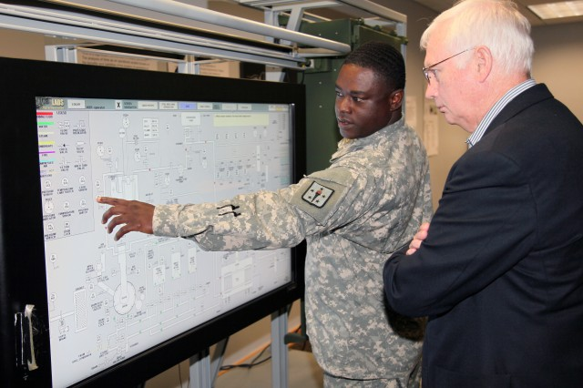 Sgt. 1st Class Johnnie H. Ambrose III, Aerial Delivery and Field Services Department instructor, demonstrates the department's laundry unit simulator to Paul Terry, House Appropriations Committee professional staff member, Aug. 15. Instructors use the simulator to provide students with the understanding of how the internal parts and processes.