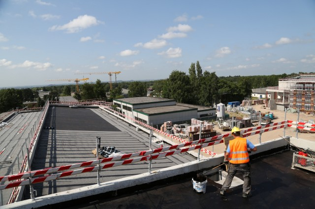 A contractor performs roofing work July 10 on top of the DODDS-Europe middle school at Supreme Headquarters Allied Powers Europe in Mons, Belgium. The U.S. Army Corps of Engineers Europe District is set to complete construction of three new U.S. facilities at SHAPE International School next year.