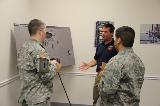 Tom Rosso, operations business manager for CBARR, talks to DoD stakeholders during a poster session.