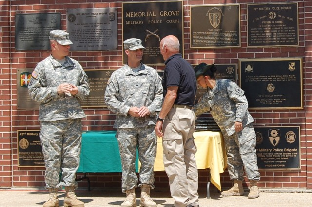 From left: Command Sgt. Maj. Michael Cosper, 701st MP Battalion command sergeant major, and Lt. Col. Curt Schroeder, 701st Military Police Battalion commander, recognize Bob Clement during the National Law Enforcement Explorer Academy graduation ceremony on Fort Leonard Wood's Military Police Memorial Grove, July 19.