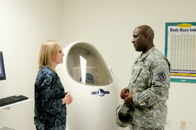 Heather Barnard, Army Wellness Center nurse educator, talks to Command Sgt. Maj. Theon Hart, U.S. Army Medical Department Activity senior enlisted adviser, about the benefits and uses of the Bod Pod. The machine is one of several state-of-the-art devices that will be used to measure fitness and health at the new AWC on post.