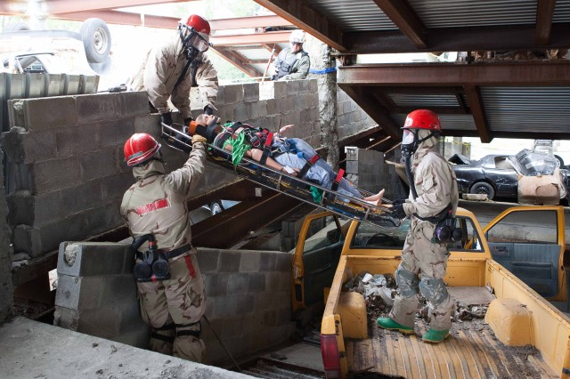 Soldiers of the 468th Engineer Detachment (Firefighters), evacuate a medical mannequin injured from the collapsed parking garage during Vibrant Response 13-2, at Muscatatuck Urban Training Center near Butlerville, Ind.