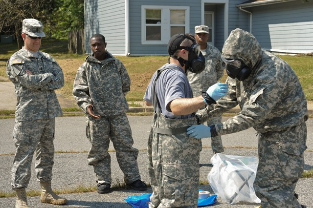 Spc. Micah Middleton, 25th Chemical Company, 20th Support Command, CBRNE, describes to Sgt. Maj. of the Army Raymond Chandler the process for decontaminating Soldiers after exiting a contaminated area, during a capabilities demonstration at Aberdeen Proving Ground, Md., Aug. 19, 2013.