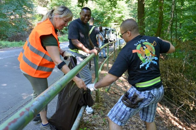 Sabine Günther, left, head of Landstuhl's parks department, helps Army Sgt. Maj. Tony Williams and Sgt 1st Class Jeremiah Delrio, to pick up trash on Luitpoldstrasse in Landstuhl