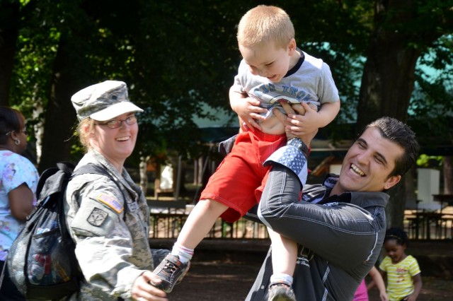 During a recent reunion at U.S. Army Garrison Kaiserslautern, Liridon Lukaj, right, a German soldier, meets with Spc. Heather Colton and her son, Riley. In April 2012, Lukaj helped rescue them from a severe traffic accident on Autobahn 6 near Einsiedlerhof, Germany. (Photo by Rick Scavetta, U.S. Army Garrison Kaiserslautern)