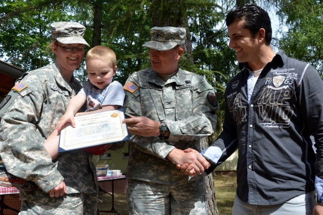 At an Aug. 15 ceremony at Pulaski Barracks, Col. Bryan DeCoster, center, commander of U.S. Army Baden-Württemberg, thanked Liridon Lukaj for his valiant efforts in rescuing Spc. Heather Colton and her son, Riley. (Photo by Rick Scavetta, U.S. Army Garrison Kaiserslautern)