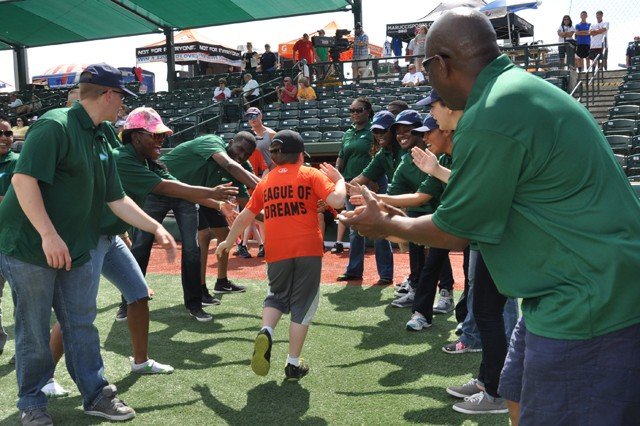 APG BOSS Soldiers, led by Garrison Command Sgt. Maj. James Ervin, far right, congratulate a League of Dreams player as he leaves the ball field during the organization's practice and game at the Ripken Experience Complex in Aberdeen Aug. 17.