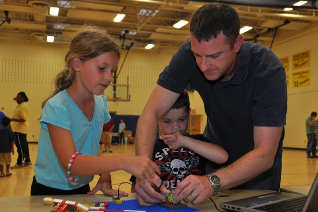 (From left) Emma Chaney, 9, and Zack Grogan, 7, look on as Zack's dad, CERDEC Electronics Engineer Nathan Grogan adjusts Chaney's Lego project during the 4-H Robotics Family Open House at the APG North (Aberdeen) Youth Center Aug. 13. The developing Heroes With Hearts Robotics group kicks off weekly meetings featuring four Lego platforms in September. For more information, contact Norma Warwick at 410-278-9059 or e-mail norma.a.warwick.naf@mail.mil.