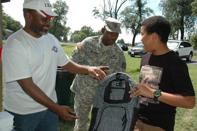 (From left) Lonzia Hawkins Jr., a CECOM civilian and Operation Homefront volunteer, presents a backpack to CW4 Antonio Belmar, from the 20th Support Command (CBRNE) and his son Antonio, Jr., during the Operation Homefront's Back-to-School Brigade at Shore Park Aug. 19.