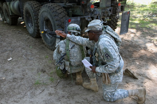 Capt. Tometrius Greer, a 4th Cavalry Brigade trainer/mentor, assists 86th  Infantry Brigade Combat Team Soldiers during the unit's recent annual training at Fort Drum N.Y. During a convoy operations training lane, the Soldiers had to correctly react to contact, pulling security and returning fire.