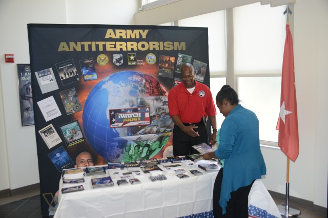 Marvin C. Solomon explains an antiterrorism awareness brochure to Tamika K. Miller during the antiterrorism display at Fort McNair, August 21, 2013