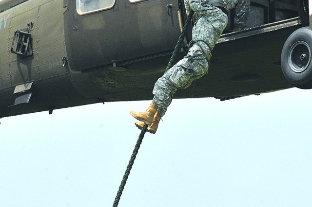 Staff Sgt. Nicole Roman, Headquarters and Headquarters Company, 6th Battalion, 101st Combat Aviation Brigade, 101st Airborne Division, rappels from the bird to complete her fast roping exercise.
