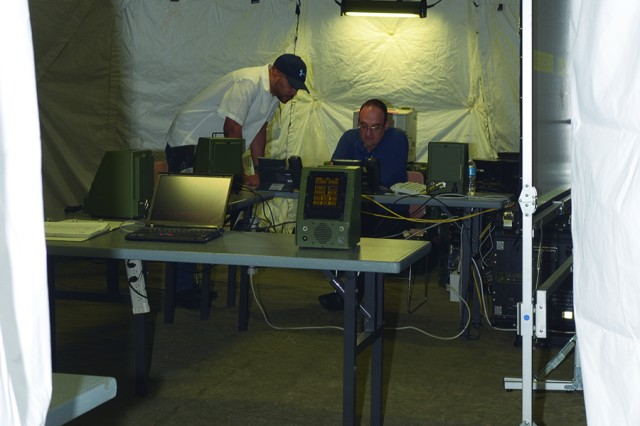 Instructor Ed Kania (seated) shows FSR Ramada Williams how to configure commercial network phones to work with the command post's communication system.  Williams is an equipment specialist (electronics) assigned to the Field Logistics Support Directorate's (FLSD) East/Europe Division, Fort Bragg, N.C.