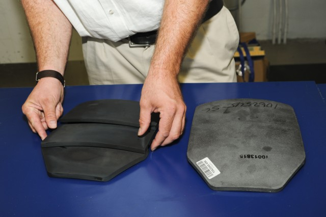 """Dr. Shawn Walsh, Agile Manufacturing Technology team leader at Army Research Laboratory, compares the """"traditional"""" one-piece ceramic body armor (right) and a prototype flexible armor concept made possible by ManTech processes at Aberdeen Proving Ground, Md., Aug. 14, 2013."""