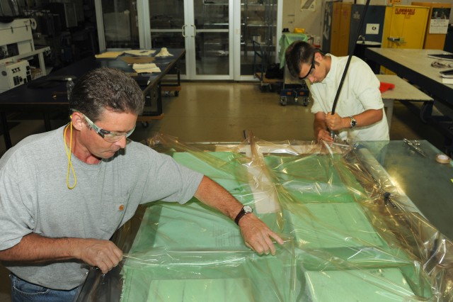 Fred Racine (left), an Army Research Laboratory contractor technician, and Rob Learsch, a Massachusetts Institute of Technology student and ARL summer intern, prepare ballistic targets from new materials supplied by ManTech contractors at Aberdeen Proving Ground, Md., Aug. 14, 2013.