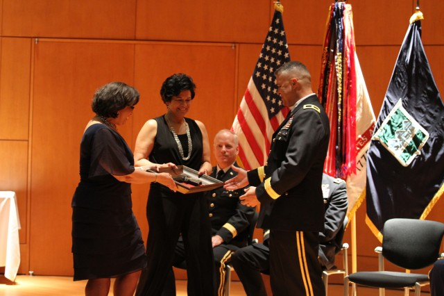 Margaret Jones (left) and Col. (ret.) Joan Williams (right), both sisters of newly promoted Brig. Gen. Richard Torres, present Torres with a replica, framed general officer pistol during his promotion ceremony at the North Carolina National Guard and North Carolina State Emergency Operations Center Joint Facility, Raleigh, N.C., on August 24, 2013. Torres has been serving as the deputy commanding general for the 80th Training Command (TASS) since May 25, 2013.