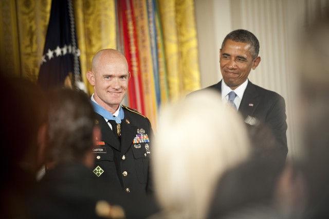 President Barack Obama and the audience applaud U.S. Army Staff Sgt. Ty Michael Carter after presenting Carter with the Medal of Honor during a ceremony at the White House in Washington, D.C., Aug. 26, 2013. Carter was awarded the Medal of Honor for actions during the Battle of Kamdesh at Combat Outpost Keating, Nuristan province, Afghanistan, Oct. 3, 2009. Carter was a cavalry scout with Bravo Troop, 3rd Squadron, 61st Cavalry Regiment, 4th Brigade Combat Team, 4th Infantry Division at the time of the battle.