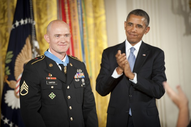 President Barack Obama applauds U.S. Army Staff Sgt. Ty Michael Carter after presenting him with the Medal of Honor during a ceremony at the White House in Washington, D.C., Aug. 26, 2013. Carter was awarded the Medal of Honor for actions during the Battle of Kamdesh at Combat Outpost Keating, Nuristan province, Afghanistan, Oct. 3, 2009. Carter was a cavalry scout with Bravo Troop, 3rd Squadron, 61st Cavalry Regiment, 4th Brigade Combat Team, 4th Infantry Division at the time of the battle.