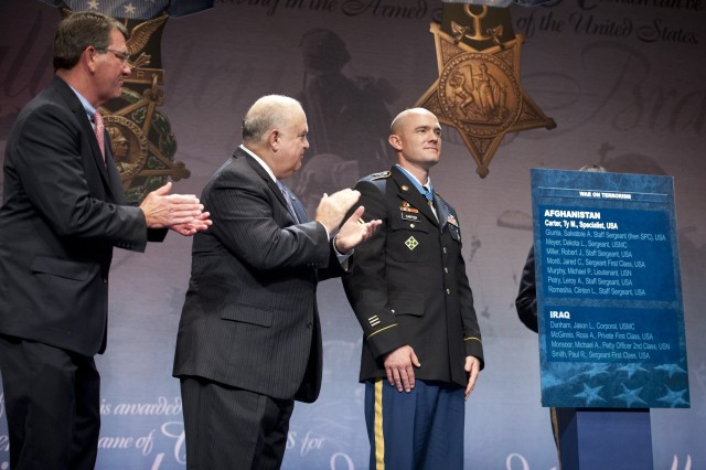 Staff Sgt. Ty Michael Carter being presented with the Hall of Heroes plaque during his induction ceremony into the Hall of Heroes at the Pentagon, Aug. 27, 2013.  From left to right stand Deputy Secretary of Defense Ashton B. Carter, Under Secretary of the Army Joseph W. Westphal, and Staff Sgt. Ty Michael Carter.