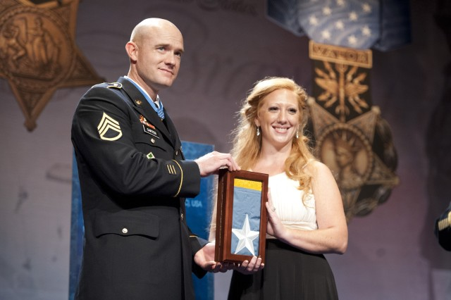 Staff Sgt. Ty Michael Carter and his wife Shannon holding the Medal of Honor Flag just after being presented with it during his induction ceremony into the Hall of Heroes at the Pentagon, Aug. 27, 2013.