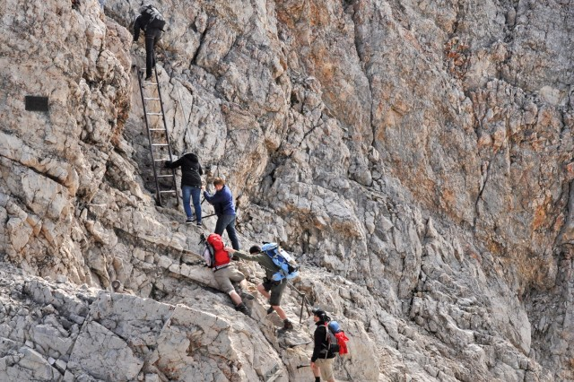 Hikers and sightseers climb a metal ladder attached to the rock face to reach the summit of the Zugspitze.