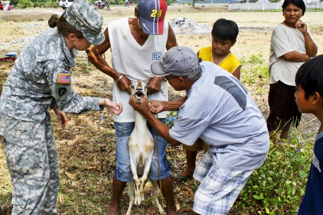 """The Army is working hard to build trust with people around the world to reduce the likelihood of future conflict where military force is necessary. U.S. Army Training and Doctrine Command personnel think the """"human domain"""" will gain as much acceptance as tanks and helicopters in military planning and mindset. Pictured here, Capt. Jennifer Scruggs, veterinarian, works with locals in the Philippines. It is just one of many examples of the Army's investment in building personal trust and relationships."""