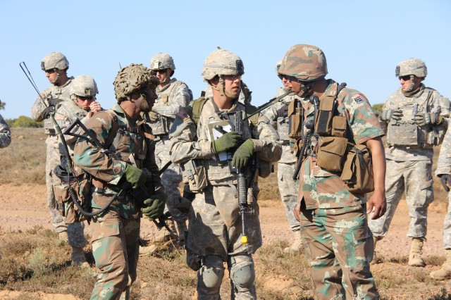 Spc. Chris Cronin, center, an infantryman with 1st Battalion, 18th Infantry Regiment, 2nd Armored Brigade Combat Team (ABCT), 1st Infantry Division, stands with South African Defense Force partners as they prepare for the next iteration of situational training exercises, July 30 as part of Exercise Shared Accord 2013. Cronin used his expertise with communication equipment to greatly aid his South African counterparts during the biennial training exercise which promotes regional relationships, increases capacity, trains U.S. and South African forces, and furthers cross-training and interoperability.