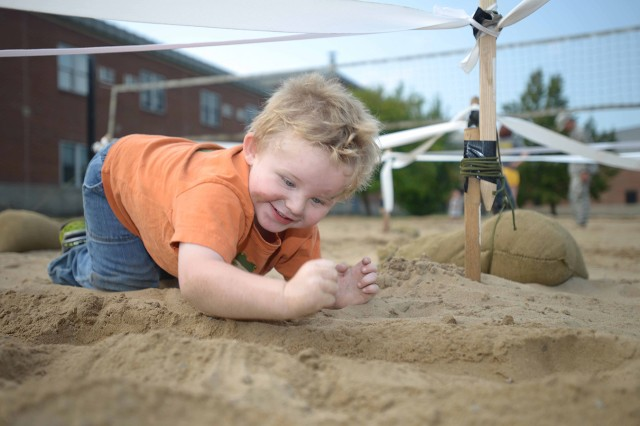 """Finn Callaghan, a """"Polar Cub"""" of 4th Battalion, 31st Infantry Regiment, 2nd Brigade Combat Team, low crawls into position during the knock out a bunker STX lane during GI Kids Day on Aug. 21."""