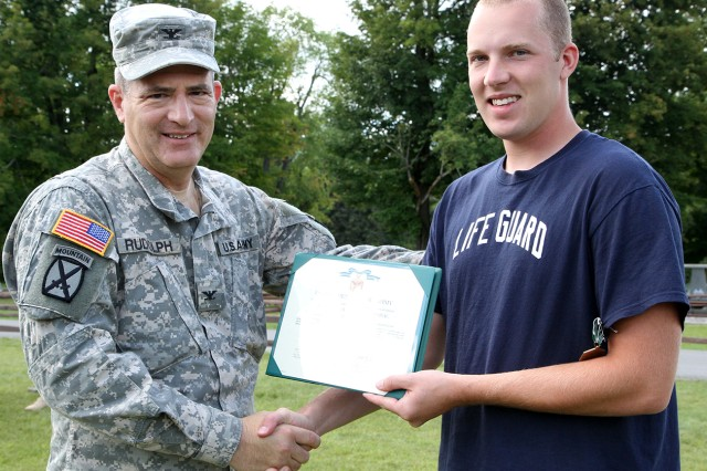 Spc. Michael Wright, assigned to A Company, 210th Brigade Support Battalion, 2nd Brigade Combat Team Rear, receives an Army Commendation Medal from Col. Robert Rudolph, commander of 2nd BCT Rear, Aug. 23 for rescuing a young boy who went out too far into the water July 28 at Remington Pond on Fort Drum.